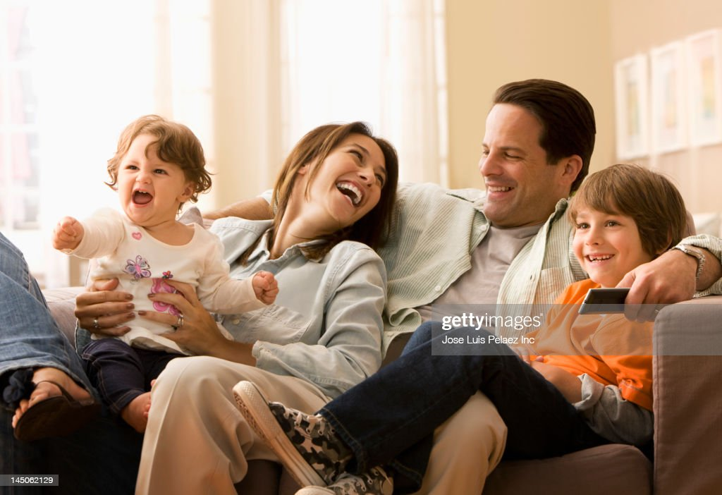 Caucasian family watching television together : Stock Photo