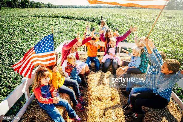 Caucasian family waving American flags on hay ride