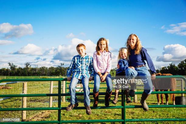 Caucasian farmer and children sitting on fence on ranch
