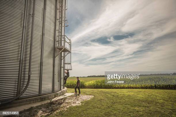 Caucasian farmer and son climbing grain silo
