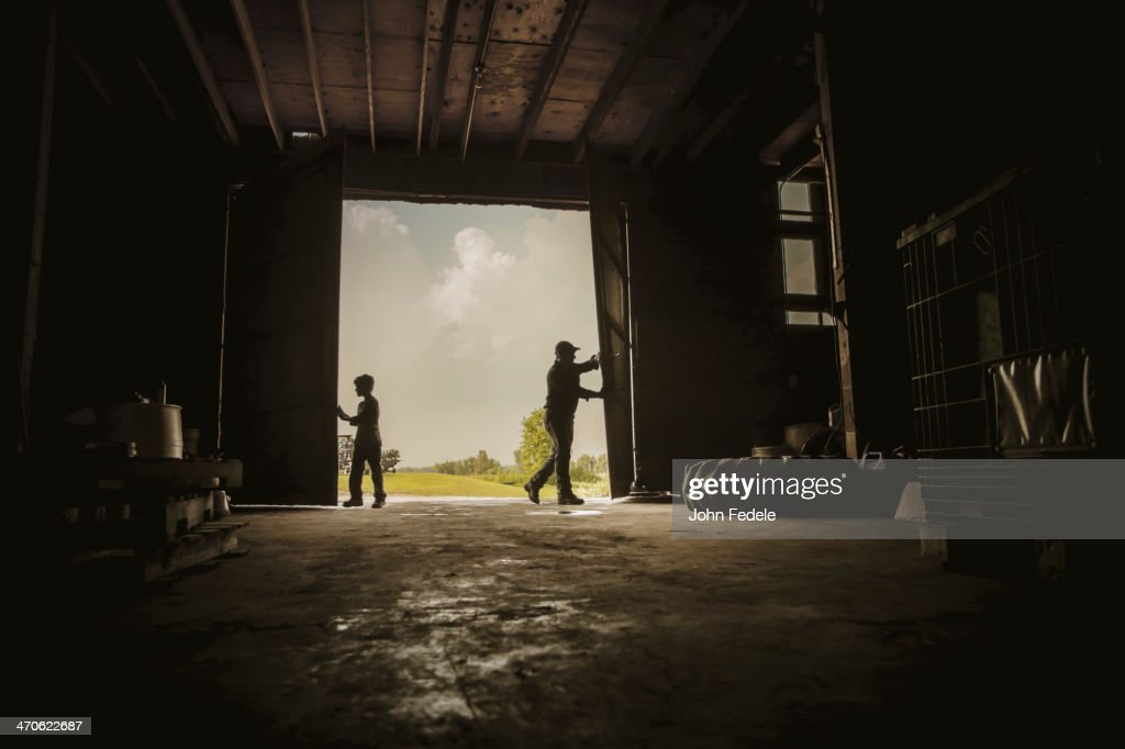 Caucasian farmer and son working in barn : Stock Photo