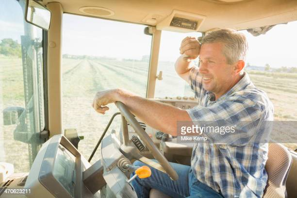 Caucasian farmer driving tractor