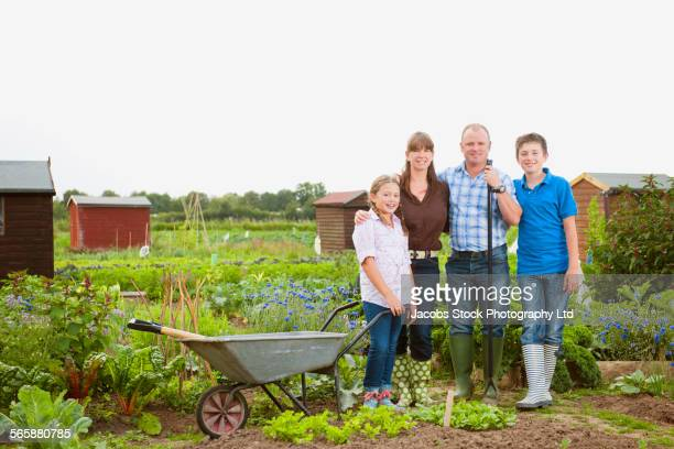 Caucasian farmer family smiling in farm fields