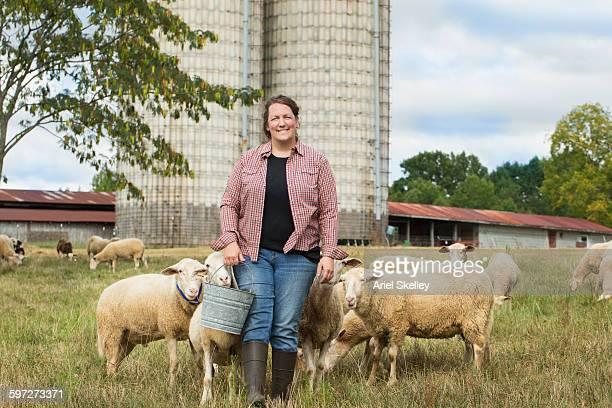 Caucasian farmer feeding sheep in field