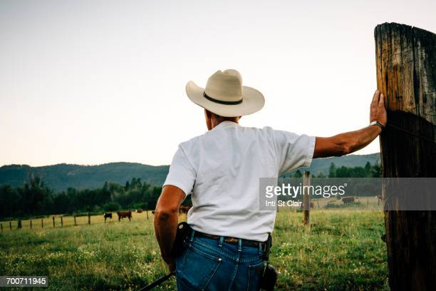 caucasian farmer leaning on wooden post - cowboy hat stock pictures, royalty-free photos & images