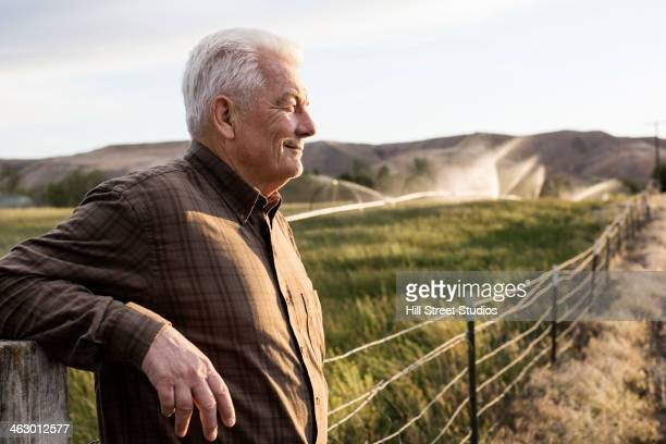 Caucasian farmer looking over fields