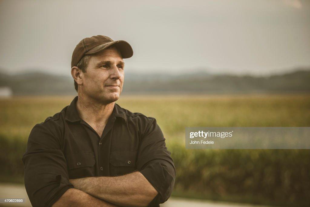Caucasian farmer overlooking crop fields : Stock Photo