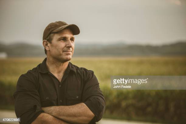 caucasian farmer overlooking crop fields - orgoglio foto e immagini stock