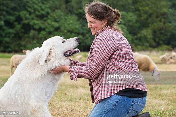 Caucasian farmer petting dog in field