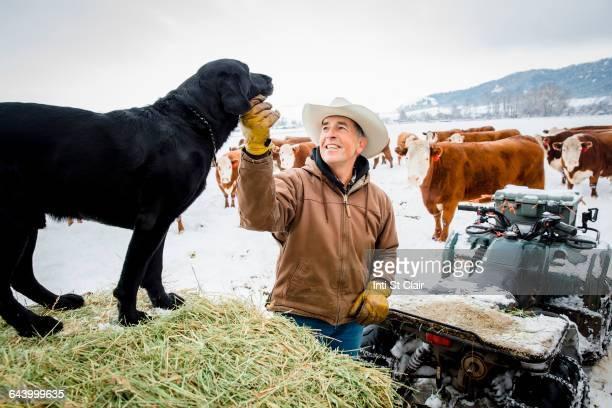 Caucasian farmer petting dog in snowy field