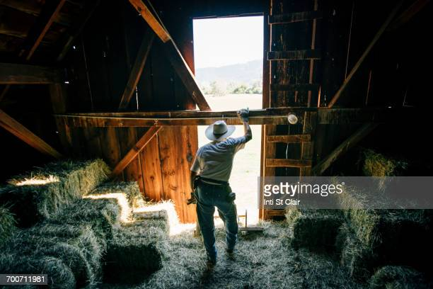Caucasian farmer resting in barn near bales of hay