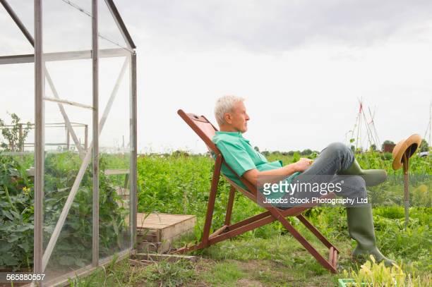 Caucasian farmer sitting in lawn chair in farm fields