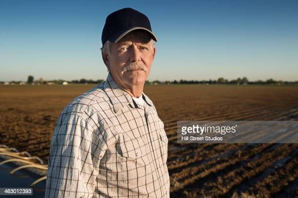 Caucasian farmer standing in irrigated field