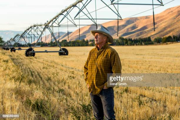caucasian farmer standing near irrigation equipment - idaho stock pictures, royalty-free photos & images