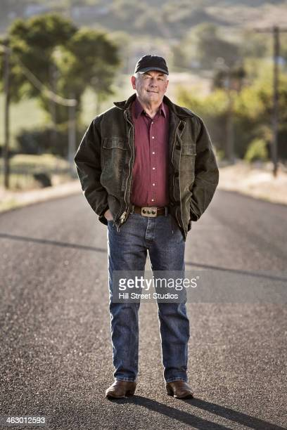 Caucasian farmer standing on rural road