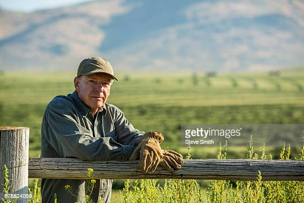 Caucasian farmer wearing gloves leaning on wooden fence