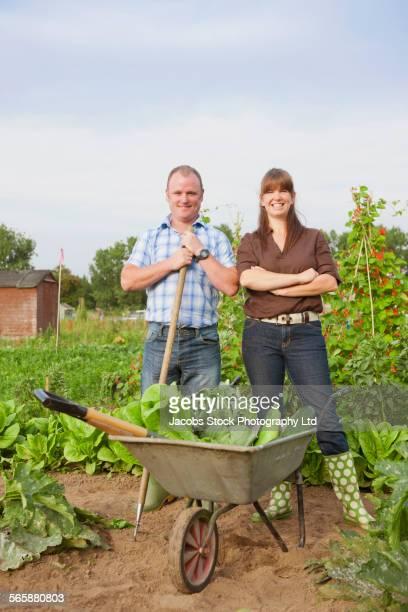 Caucasian farming couple with wheelbarrow of vegetables