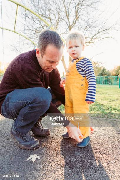 Caucasian father adjusting pants for son