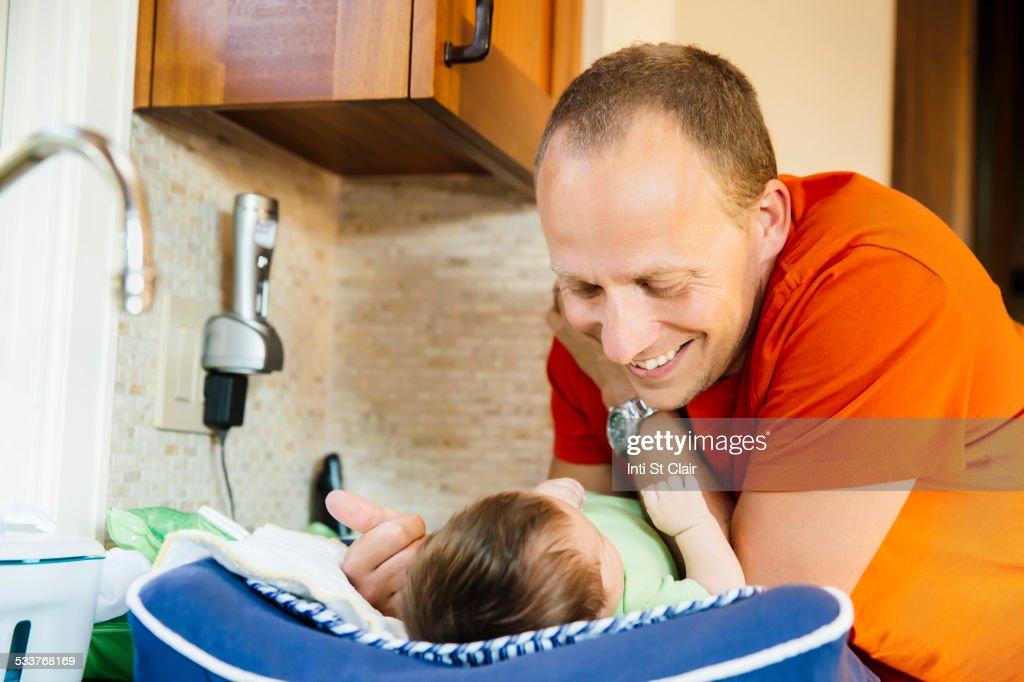 Caucasian father admiring baby boy in kitchen : Foto stock