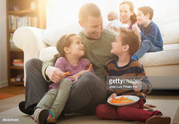 Caucasian father and children eating snack