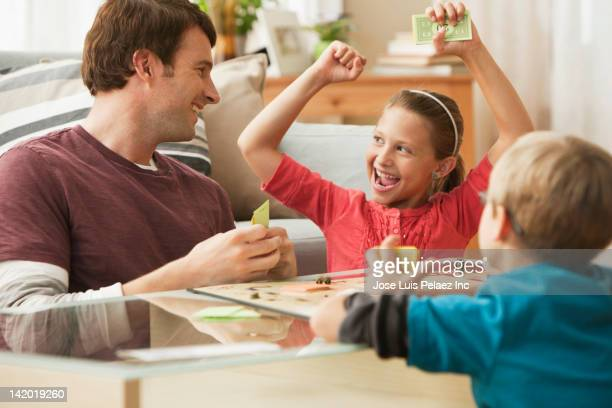 caucasian father and children playing board game - leisure games stock pictures, royalty-free photos & images