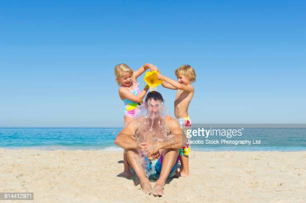Caucasian father and children playing on beach