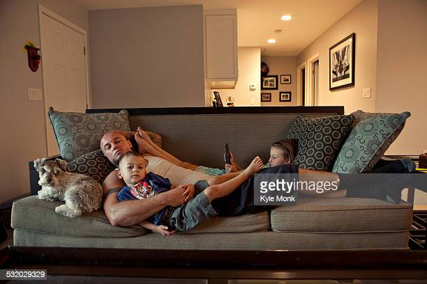 caucasian father and children relaxing on sofa - family watching tv stock pictures, royalty-free photos & images