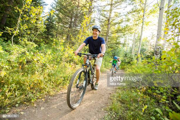 caucasian father and children riding mountain bikes - lane sisters stock photos and pictures