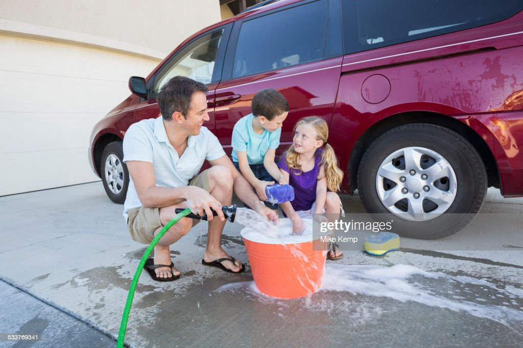 Caucasian father and children washing car in driveway : Foto stock