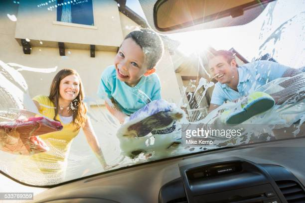 Caucasian father and children washing car windshield