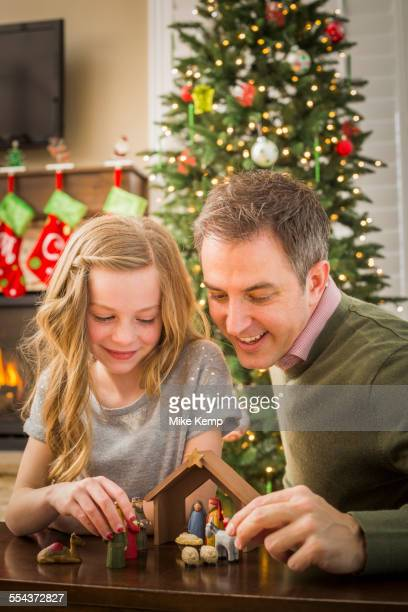 caucasian father and daughter arranging nativity at christmas - nativity stock photos and pictures