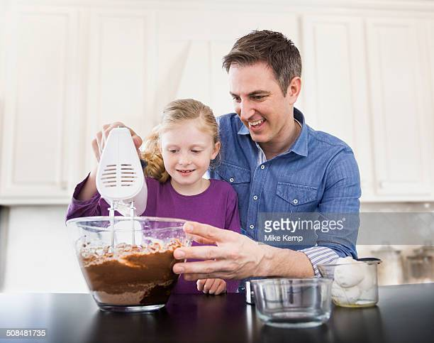Caucasian father and daughter baking together