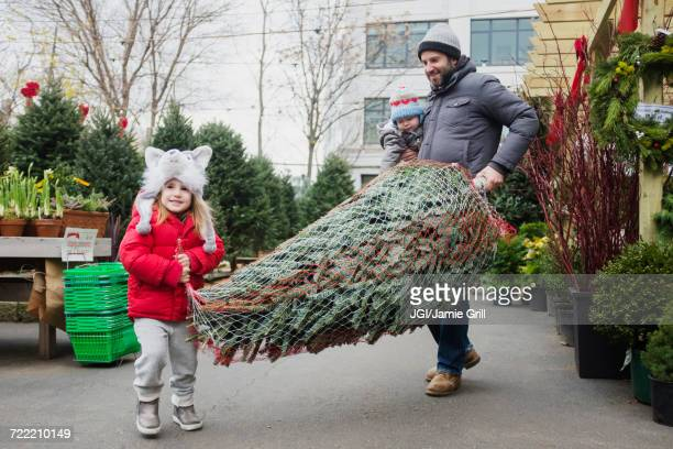 Caucasian father and daughter carrying wrapped Christmas tree