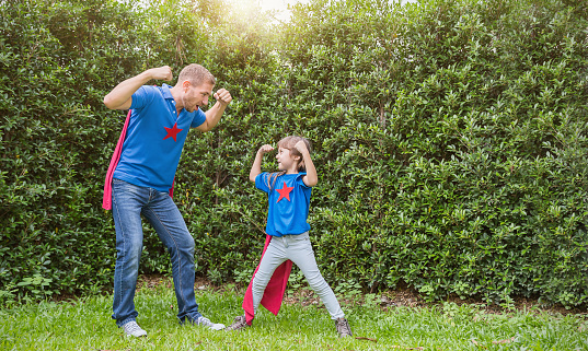 Caucasian father and daughter child girl playing in the spring or summer green park outdoors. Happy family love together single dad lifestyle father's day holiday concept 1058371760