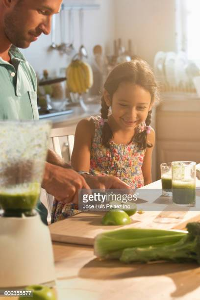 Caucasian father and daughter chopping vegetables