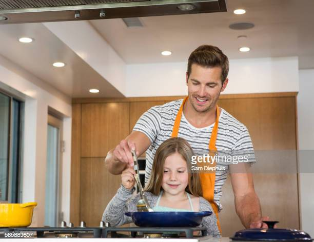 Caucasian father and daughter cooking in kitchen