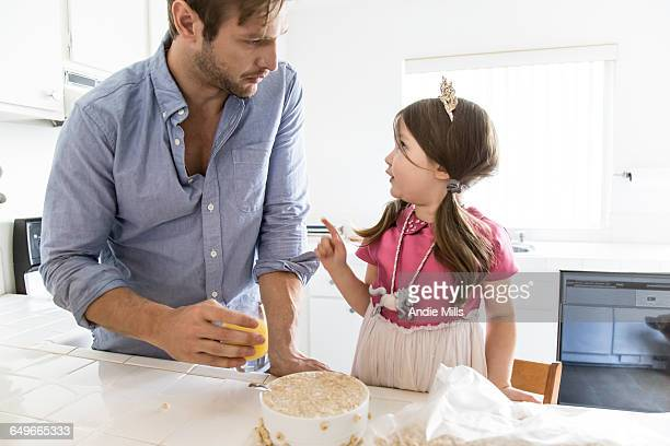 Caucasian father and daughter eating cereal in kitchen