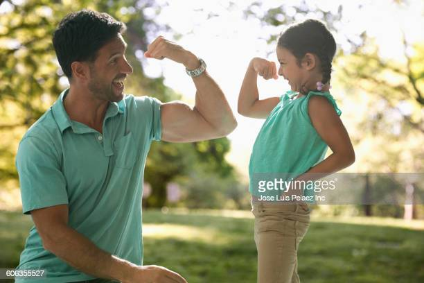 caucasian father and daughter flexing muscles - flexing muscles stock pictures, royalty-free photos & images