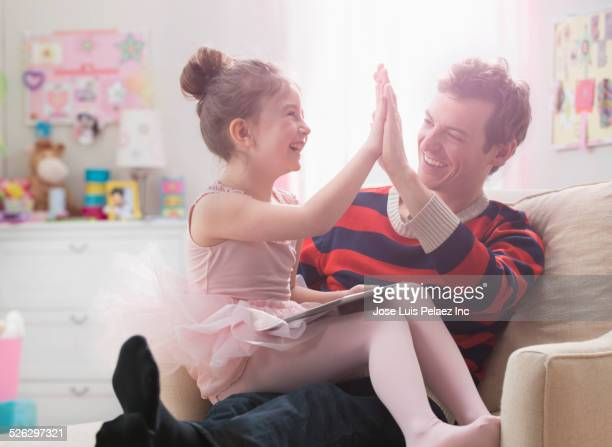 Caucasian father and daughter high fiving in bedroom