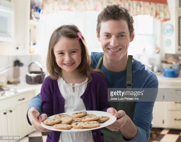 Caucasian father and daughter holding cookies in kitchen