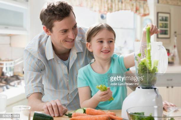 Caucasian father and daughter juicing vegetables