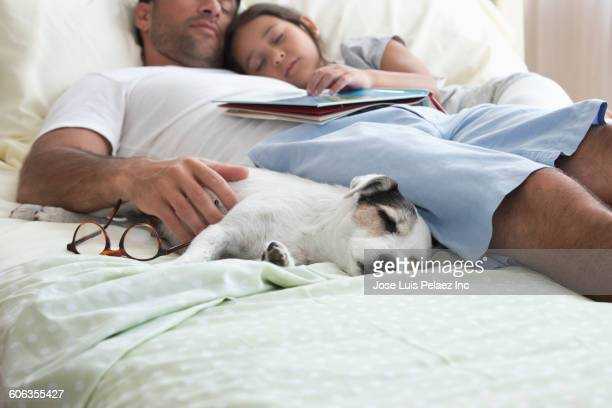 Caucasian father and daughter napping on bed