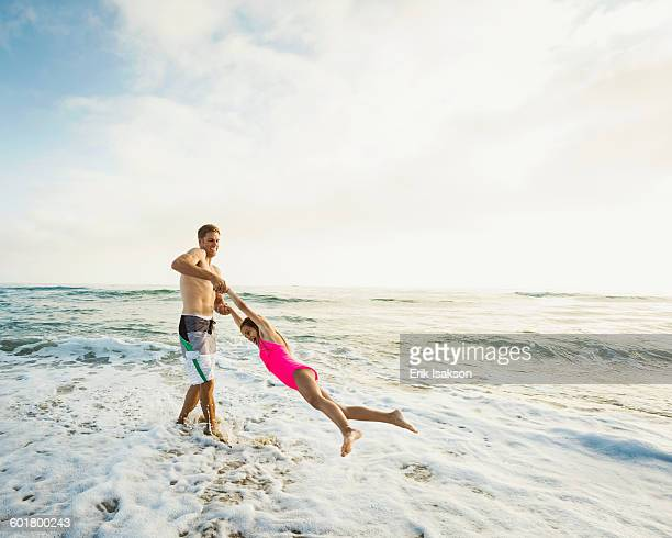 caucasian father and daughter playing in waves on beach - california strong stock photos and pictures