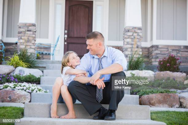 Caucasian father and daughter sitting on front stoop