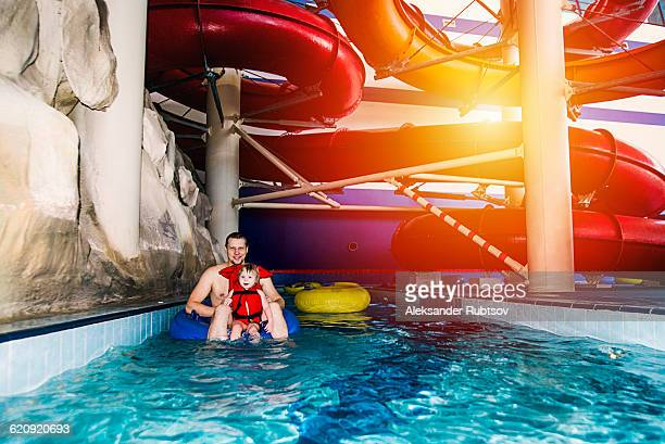 Caucasian father and daughter swimming under water park slide