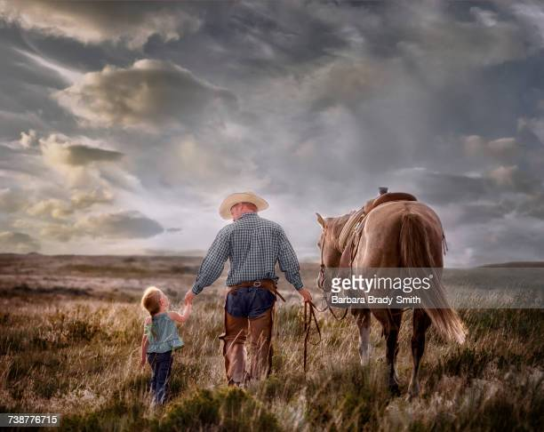 Caucasian father and daughter walking horse in field