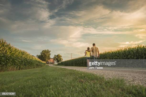 Caucasian father and daughter walking on dirt path by corn field