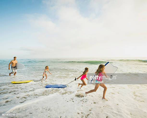 caucasian father and daughters playing in waves on beach - orange county california stock pictures, royalty-free photos & images