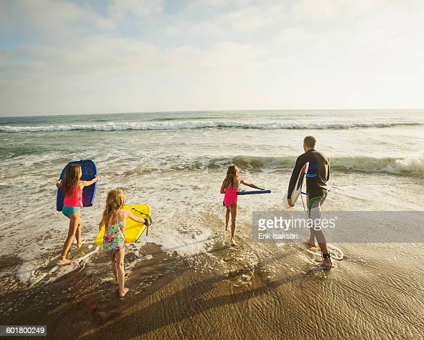 caucasian father and daughters playing in waves on beach - san clemente california stock pictures, royalty-free photos & images