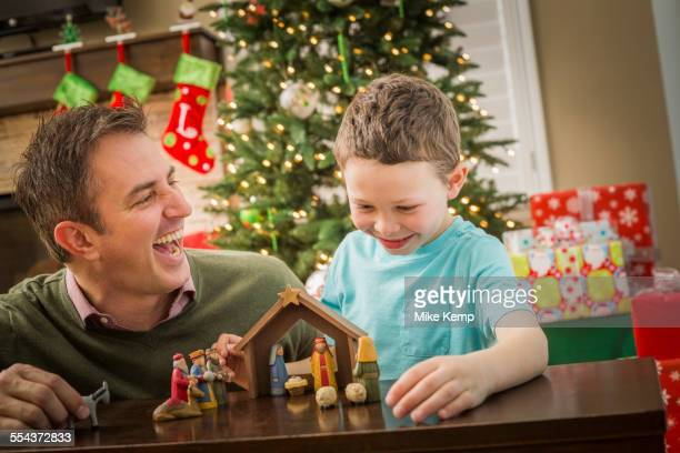 Caucasian father and son arranging nativity at Christmas